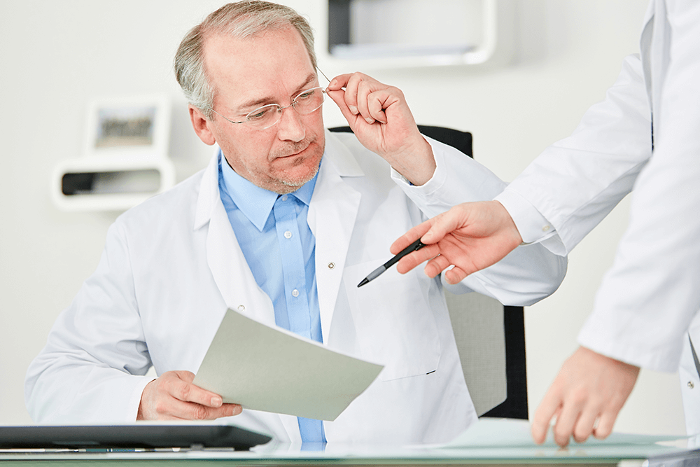 professional man, doctor, looking at paperwork with an employee pointing to it with a pen