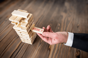 Man's hand pulling out a wooden block showing business risk