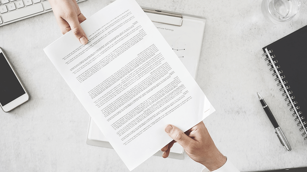 man handing over paper with employee benefits packages listed